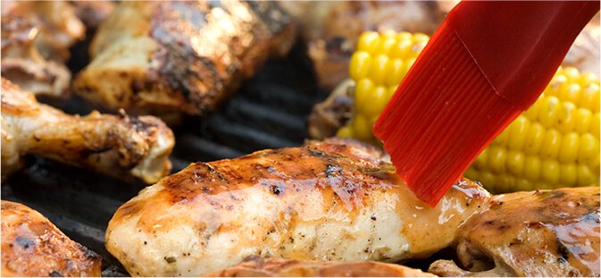 Grilled chicken on barbecue with basting brush