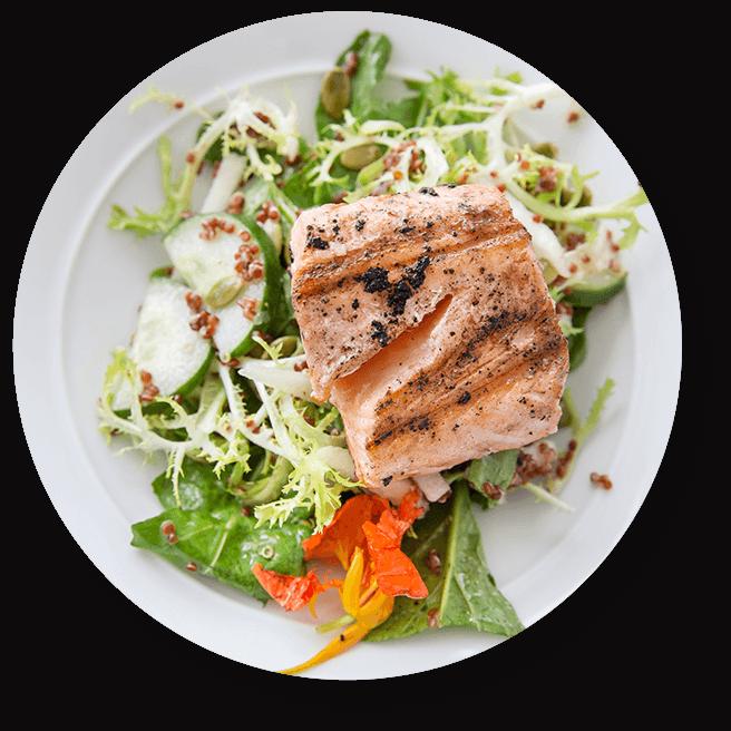 Assiette de saumon grillé sur salade avec vinaigrette citronnée à la moutarde
